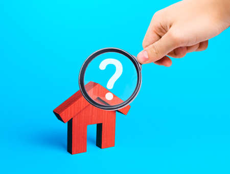 Realtor examines houses through a magnifying glass. Real estate market review. Quality of housing and availability of infrastructure. Verification of declared compliance. Price, location, legality Archivio Fotografico