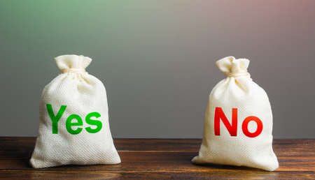 Two bags with Yes and No. Risk planning. Advantages and disadvantages. Useful and harmful properties. Decision making, evaluating profit and consequences. Choice between positive and negative answer. Archivio Fotografico