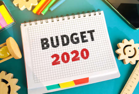 Notebook with inscription Budget 2020. Accumulating money and planning a budget. Business and finance. Loan, deposit, credit. Investments. Goals, income. Gears, hourglass, telephone