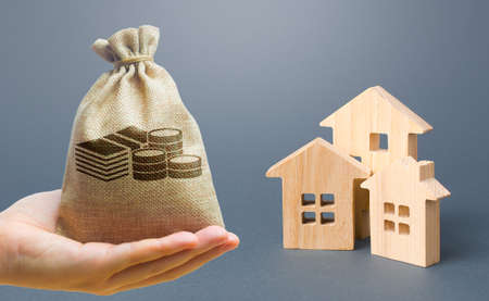 Money bag, wooden houses on a gray background. Buy purchase and sale of housing, rental. Community owners of apartments and houses. Construction industry, maintenance and utilities. Mortgage Archivio Fotografico - 167172815