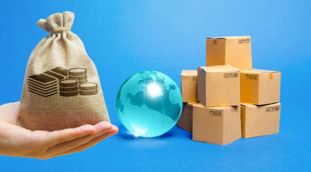 Money bag, blue glass globe and cardboard boxes. International world trade distribution. Delivery of goods, shipping. Global economy, import export freight traffic. Globalization markets.