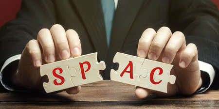 Wooden puzzless with the word SPAC - Special purpose acquisition company. Simplified listing of company, merger bypassing stock exchange IPO. Assessment of benefits and risks of investments Archivio Fotografico