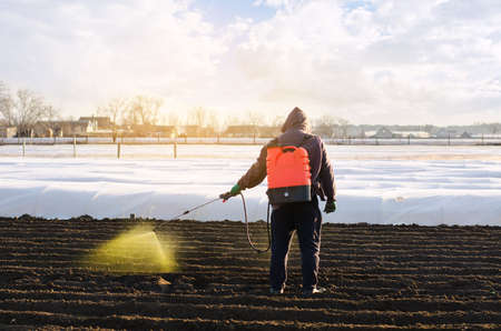 The farmer treats the field from weeds and grass for growing potatoes. Use chemicals in agriculture. Harvest processing. Agriculture and agribusiness. Protection and care. Growing vegetables Archivio Fotografico - 167172821