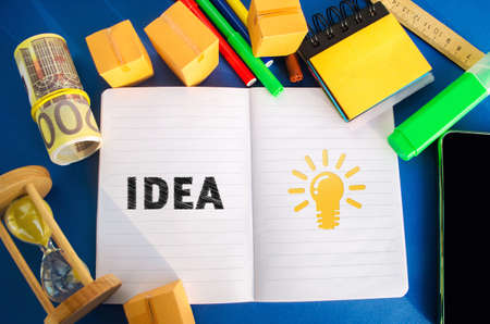 Notebook with word Idea and light bulb idea icon. Concept of new innovation ideas and discoveries. Vision, planning. Strategy and management. Business and finance. Flat lay