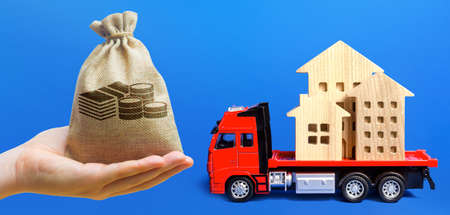 Money bag, red freight truck loaded with figure houses. Relocation of buildings and monuments. Cargo transportation, delivery service. A moving company. Infrastructure and logistics industry.