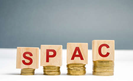 Wooden blocks with the word SPAC - Special purpose acquisition company. Simplified listing of company, merger bypassing stock exchange IPO. Assessment of benefits and risks of investments Archivio Fotografico