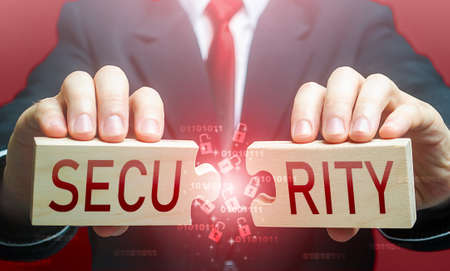 Man breaks the puzzle with word SECURITY. Security breach, hacker attack and data leak. Bypassing protection, hacking networks. Damage, disruption of work. Hybrid war. Vulnerability risks. Signaling Archivio Fotografico