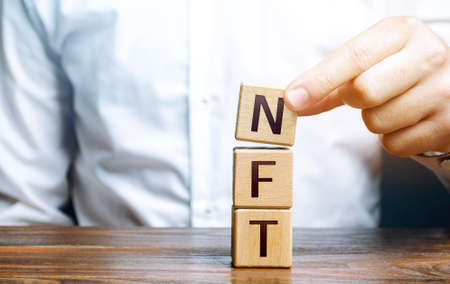 Man puts together word NFT from blocks. NFT non-fungible token. Selling digital art assets through internet auctions. Blockchain technology. Monetization, investment in cryptographic tokens Archivio Fotografico