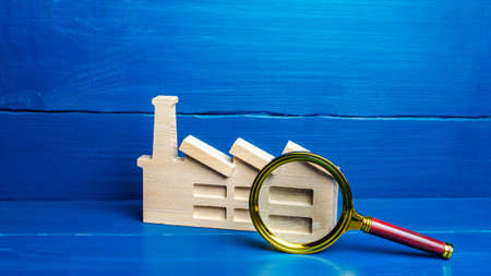 Figurine of an industrial factory plant and a magnifying glass. Big business monitoring concept, emission control. Property appraisal, enterprise audit. Compliance with sanctions policy. Analysis work
