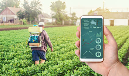 A hand with a phone on background of a farmer with agriculture smoke fog spraying machine. Crop plant care and protection from pests and fungal infection. Control of use of chemicals growing food. Archivio Fotografico