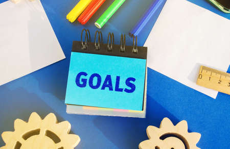 Notes with inscription Goals. Planning, plans and tasks. New business ideas. Setting goal, target. Motivation, inspiration concept. Gears, ruler, markers. Flat lay