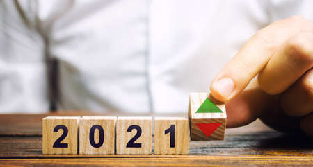 Businessman puts wooden blocks 2021 and up or down arrow. Summing up the year. Financial and economic results. Report, reporting concept. Surplus. Economic recovery. Successful business