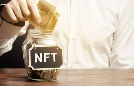 Hand puts dollar bills in glass jar with the word NFT. Non-fungible token. Digitally represented product or asset. Selling digital assets and art through auctions. Blockchain technology.