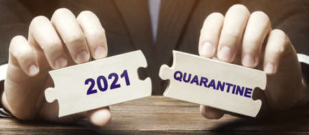 A man collects wooden puzzles with the words 2021 and Quarantine.