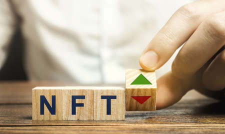 Woodens block NFT and up, down arrow - non-fungible token. Digitally represented product or asset. Selling digital assets and art through auctions. Blockchain technology. Monetization, investment
