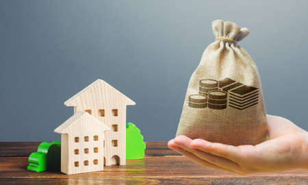 Money bag, figures of residential buildings on a gray background. Buy purchase and sale, housing rental. Community owners of apartments. Construction industry real estate, maintenance utilities. Mortgage loan