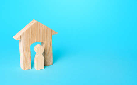 A figurine of a man in a wooden house. Affordable housing, realtor services. Rent of real estate. Mortgage loan. Building maintenance. Rent of apartments and houses. Minimalism