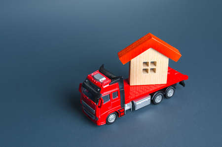 Truck transporting a house. Delivery services to another house. A moving company. Transportation of real estate. Resettlement program for new housing. Construction industry. Building insurance. Stock fotó