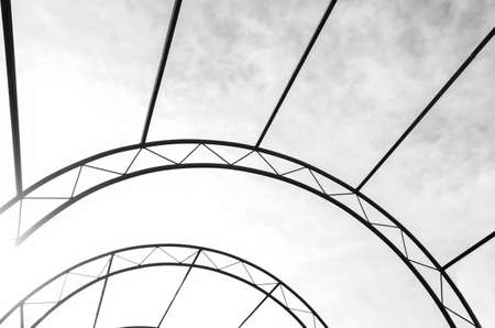 Abstraction of an of a arc metal structure on a sky background. Architecture, decorative elements. Constructive trusses. Stock fotó