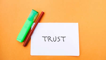 A note with the inscription Trust and a markers. Trust relationships between business partners, friends, relatives. Respect and authority. Confidence in a person. Reliable partner