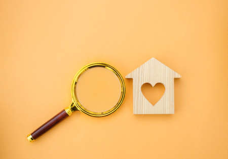 Magnifying glass and wooden house. House searching concept. Home appraisal. Property valuation. Choice of location for the construction. Search for housing, apartments. Real estate appraiser services Stock fotó