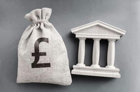 Pound sterling money bag and government building. Business and finance concept. Deposit, loan and investment in to the bank. Credit. Help from the state. Subsidies and Benefits. Budget. Stock fotó