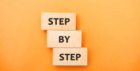 Wooden blocks with the words Step by Step. Business growth and strategy concept. Planning process, goals, objectives. Vision and ideas. Ahievement Stock fotó