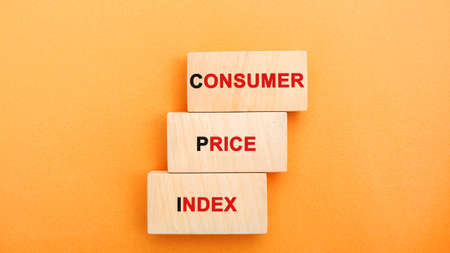 Wooden blocks with the words Consumer price index. Measuring the average level of change in prices for goods and services. Business and finance concept