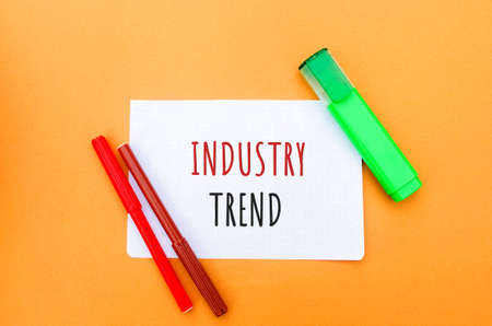 Notes with the inscription Industry trend and a markers. The concept of searching for new ideological trends and tendencies. Exclusive modern trend. Popular and relevant topics. Stock fotó