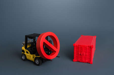 A forklift carries a no sign and a shipping container. Global container shortage. Logistics problems. Restrictions on import and export. Ban on transfer of goods, trade wars. Sanctions, Limiting Foto de archivo