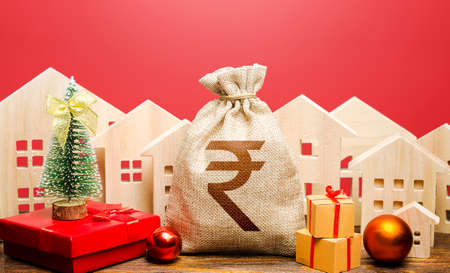 Indian rupee money bag and houses in a New Year's atmosphere. Increase in investment attractiveness, prosperity. Bank deposit, credit. Promotions, offers. Xmas winter holiday. Mortgage loans. Stock fotó