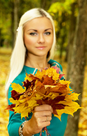 armful: Beautiful blonde in the autumn weather holding an armful of leaves, one Stock Photo