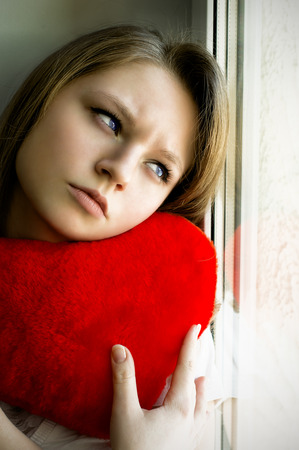 love hurts: Beautiful girl longing for her beloved and keeps the heart, sitting at the window Stock Photo