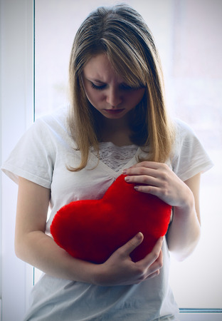 love hurts: Beautiful girl longing for her beloved, sitting at the window Stock Photo
