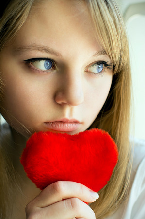 love hurts: sad girl looking out the window waiting for her husband, in the house