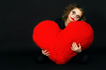 love hurts: painted girl holding a big heart on a black background
