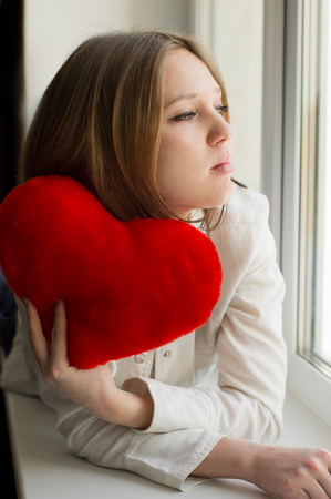 love hurts: Beautiful girl is sad, sadness due the guy, keep heart sit near the window