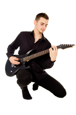 a handsome guy plays the electric guitar isolated on white background photo