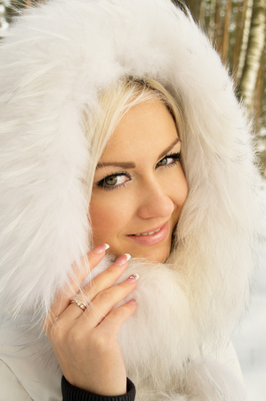 beautiful girl in the hood in the forest in winter Stok Fotoğraf