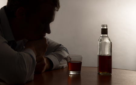 A young man alcohol abuse, on the table is alcohol 写真素材