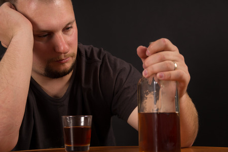 A young man alcohol abuse, on the table is alcohol photo