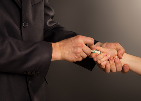 accepting: business person accepting a bribe, on a black background Stock Photo