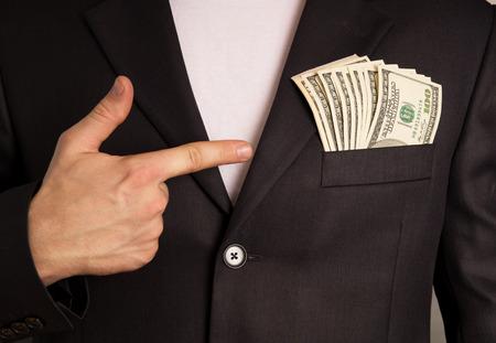 Businessman indicates money in your pocket, on a black background Stok Fotoğraf