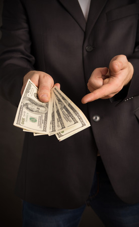 wants: Businessman wants so you took the money, on a black background Stock Photo