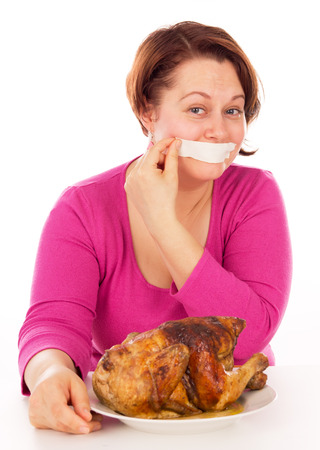 not full: Full woman on a diet does not stand up and want to eat chicken, isolated on white background