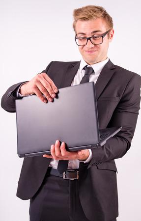 successes: L'uomo d'affari in tuta gioire dei successi di e in possesso di un computer portatile, su uno sfondo grigio