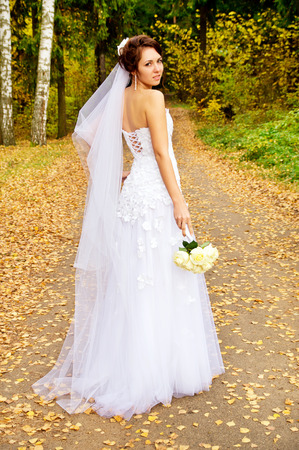 beautiful bride worth with a bouquet on nature photo
