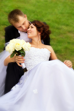 beautiful newlyweds lay on the grass on nature photo