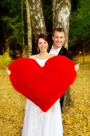newlyweds holding a heart on nature photo