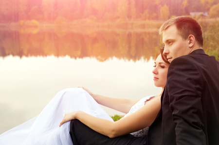 newlyweds lay on the grass at the lake on nature photo